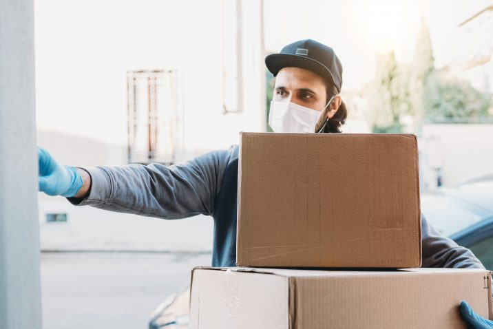 Delivery man is ringing the bell to deliver two cardboard boxes. He's wearing a face mask and protective gloves.